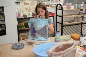 A girl making a clay sculpture