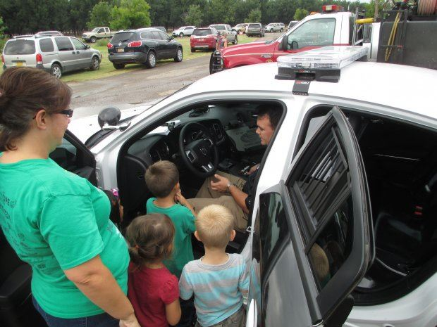 Kids Being Shown Police Car by Officer