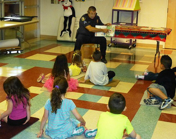 Officer Reading Book to Young Children