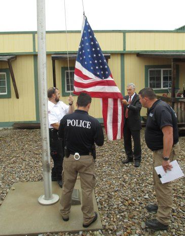 Police and Staff Raising American Flag