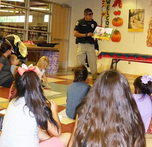 Kids Sitting on Floor Listening to Officer Read